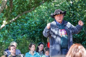 Brant Secunda speaks to a crowd of people in nature